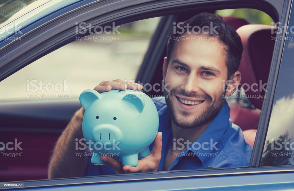 Man sitting inside his new car holding piggy bank stock photo