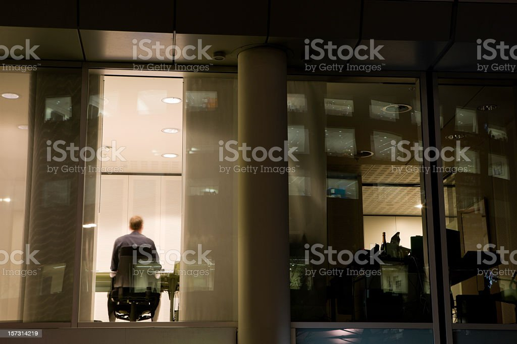 Man sitting inside working late at night stock photo