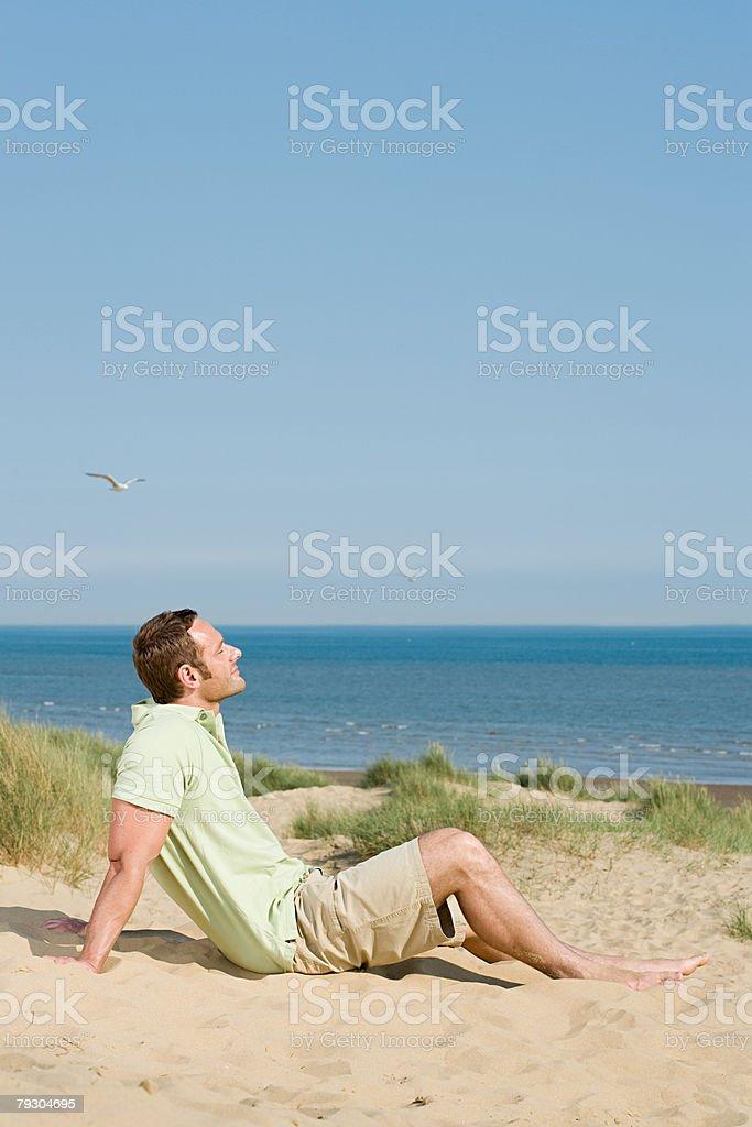男に座るビーチ ロイヤリティフリーストックフォト