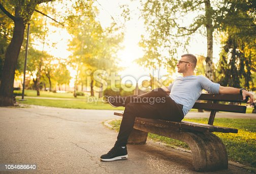 Young man sitting on bench in a park and relaxing
