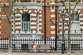 istock Man, sitting on a bench, reading a paper in Palace Green Quarter, London, United Kingdom 1163337106