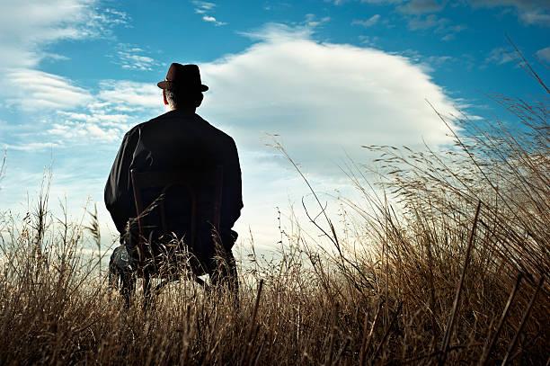 Mann sitzt auf einem Stuhl in der Landschaft – Foto