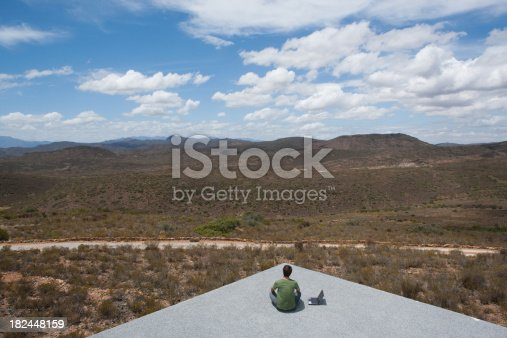 istock Man sitting on a corner with his laptop computer 182448159
