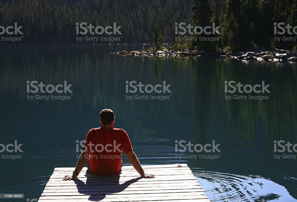 Man Sitting on a Dock in the Mountains royalty-free stock photo