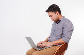 istock man sitting on a high chair and working on a laptop 505396949