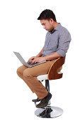 istock man sitting on a high chair and working on a laptop 505396951