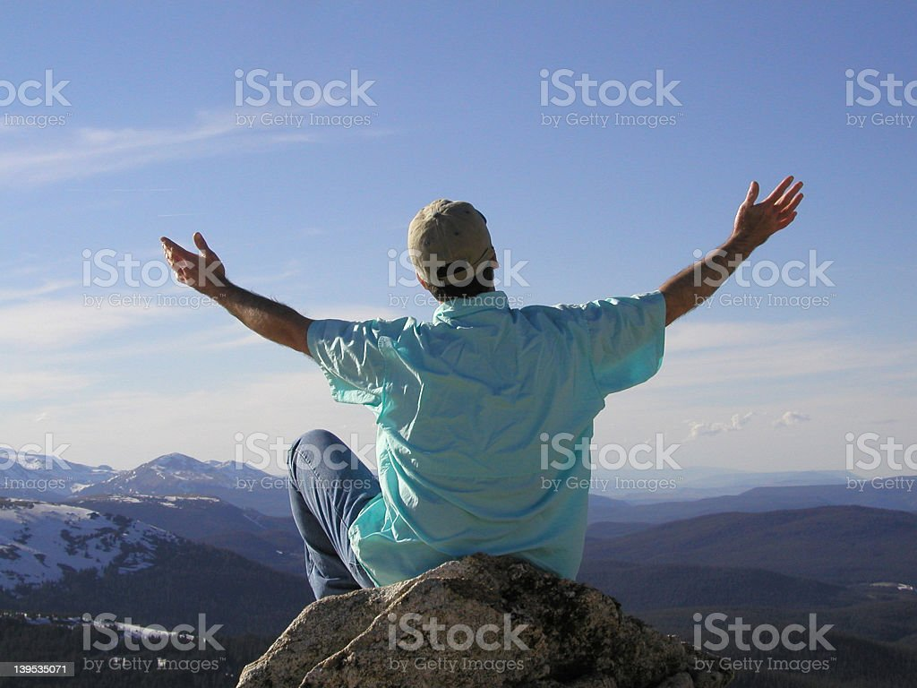 A man sitting on a mountain top opening his arms to the sky stock photo