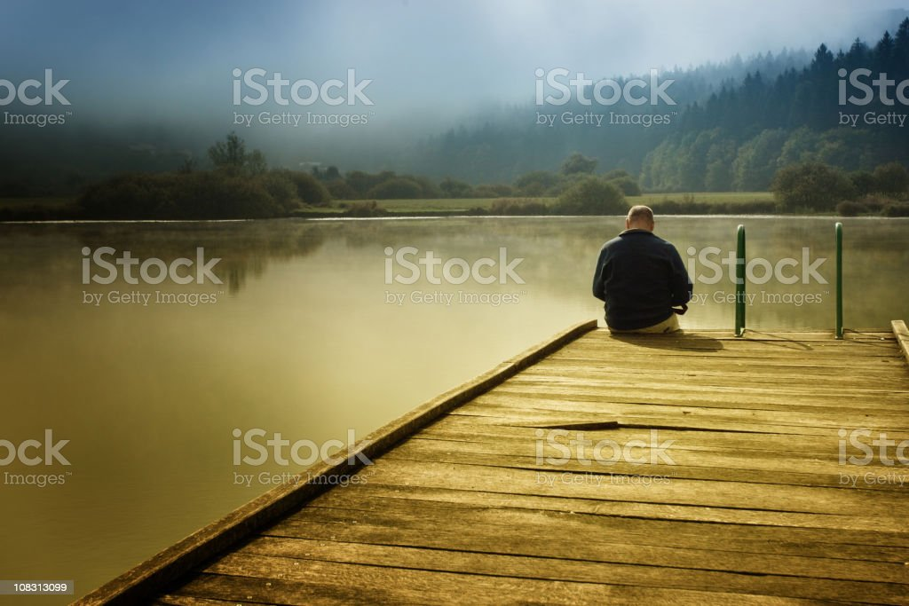 Man sitting on a pier royalty-free stock photo
