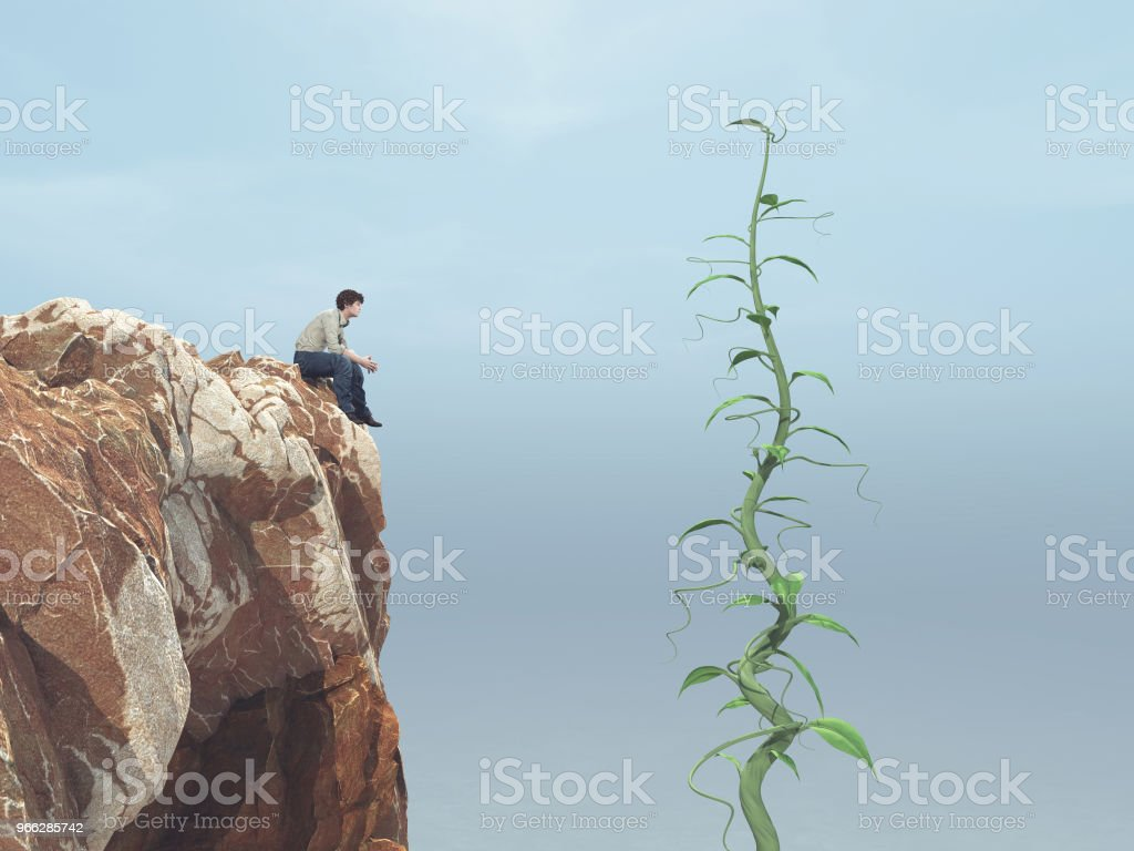 Man sitting on a rock and looking up to his big beanstalk growing up to the sky stock photo