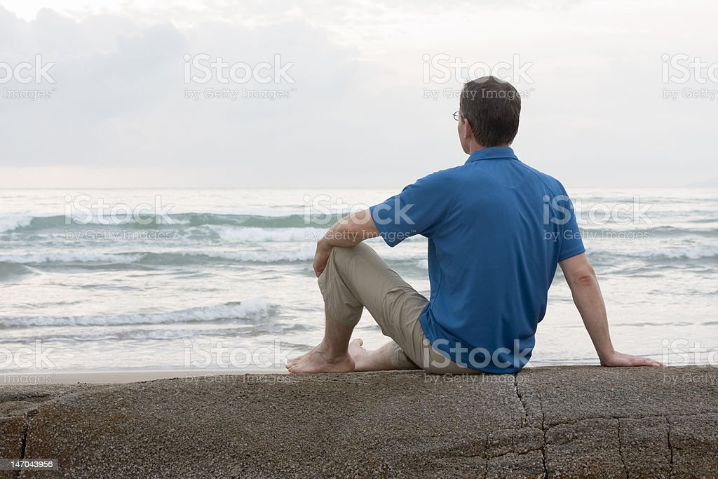 Man sitting on a rock at the sea royalty-free stock photo