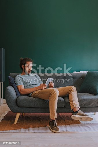 Working from home: young businessman doing business online on his digital tablet.