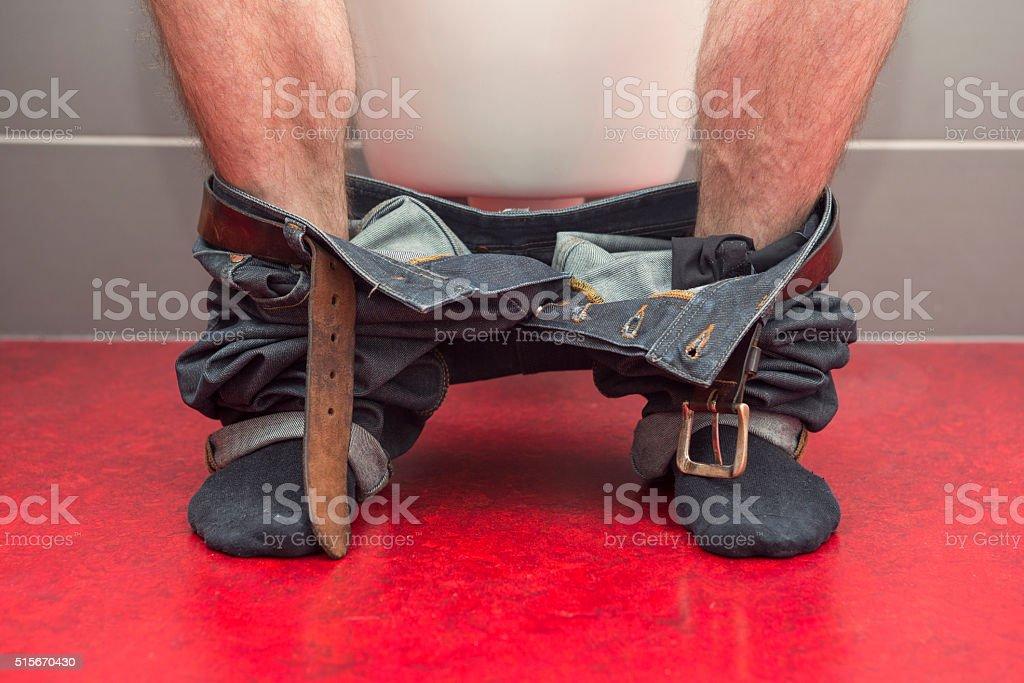 man sitting on a toilet stock photo