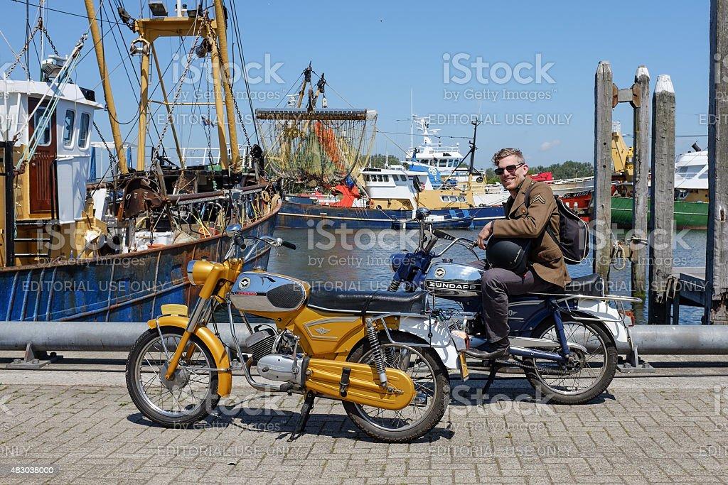 Man sitting on a vintage Zundapp motorbike. stock photo