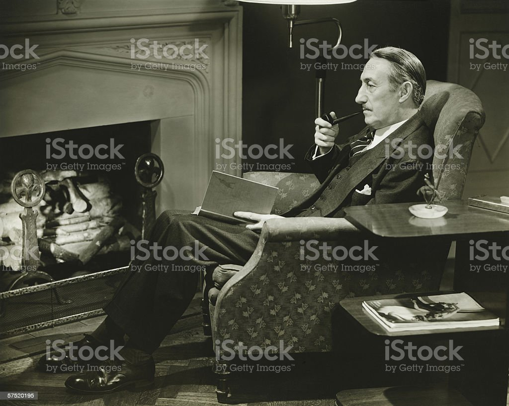 Man sitting on armchair in front of fireplace, (B&W) stock photo