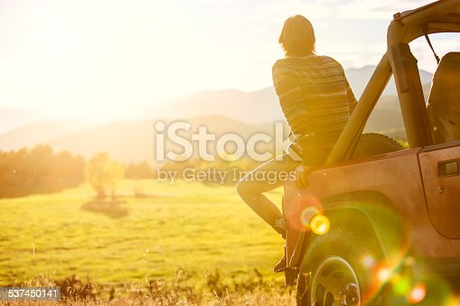 Rear view of young man sitting on back of SUV parked at field