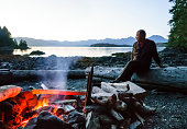 Man sitting on beach by a campfire in the wilderness, Broken Group Islands, Barkley Sound, Pacific Rim National Park, Canada. Middle aged mature people enjoying outdoor adventures. Selective focus on fire.