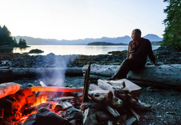 man sitting on beach by a campfire in the wilderness, broken group islands, barkley sound, pacific rim national park, canada. middle aged mature people enjoying outdoor adventures. selective focus on fire. - wilderness stock pictures, royalty-free photos & images