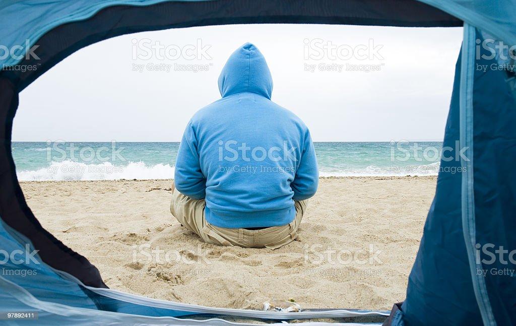 man sitting on beach looking at sea. royalty-free stock photo