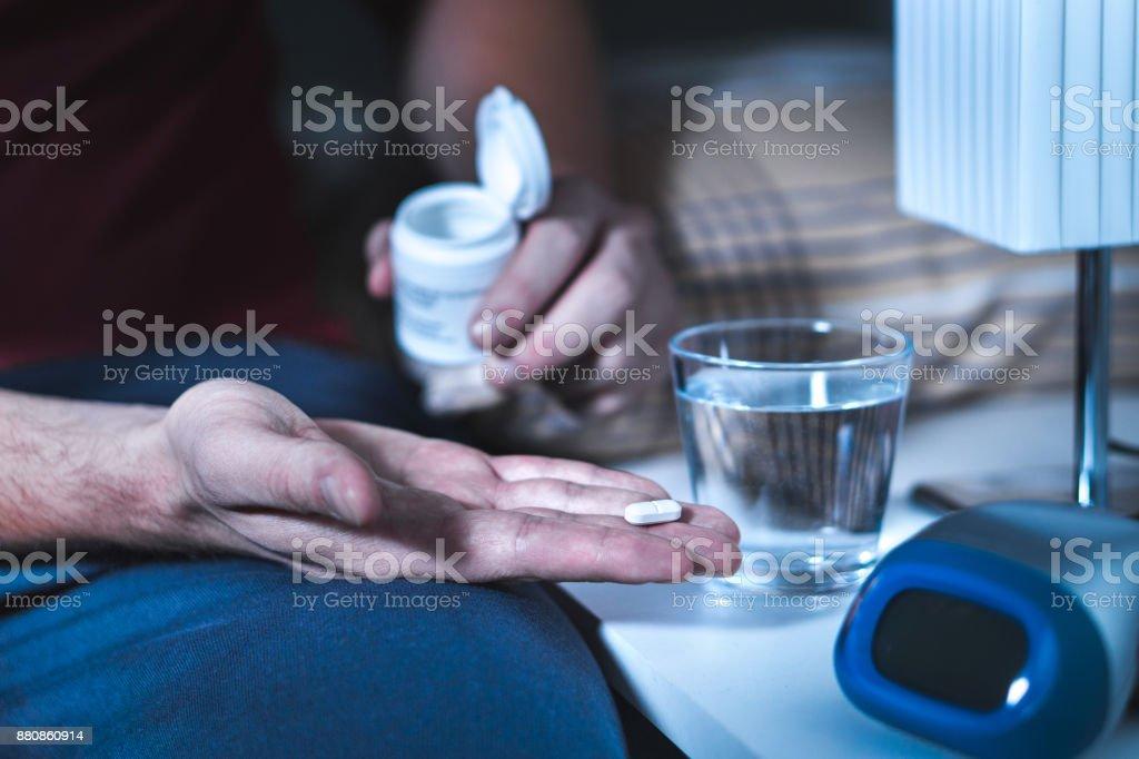 Hombre sentado en la cama a punto de tomar el Somnífero o medicina de noche. Sufren de insomnio. - foto de stock