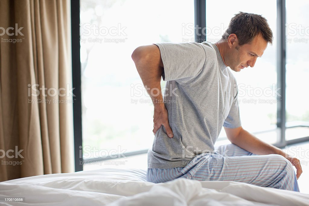 Man sitting on bed with backache   30-39 Years Stock Photo