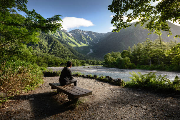 Man sitting on bench alone in Kamikochi national park stock photo