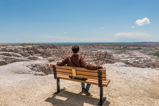 istock Man sitting on bench looking at eroded Badlands canyons 610033672