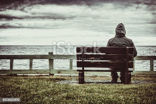 Man sitting on bench overlooking sea