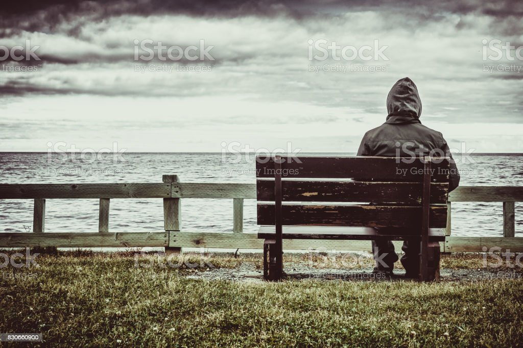 Man sitting on bench overlooking sea stock photo