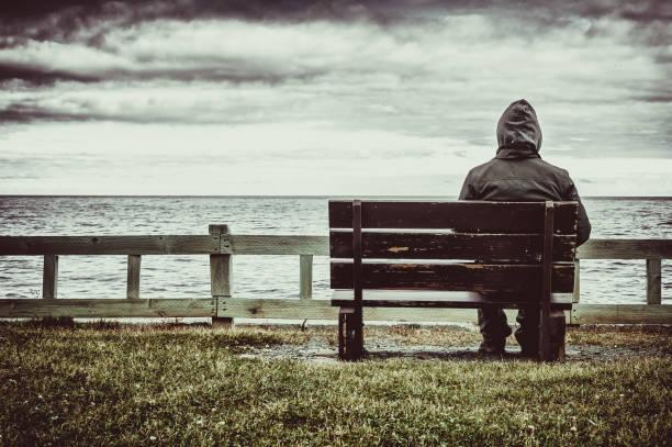 mann sitzt auf der bank mit blick auf meer - depression stock-fotos und bilder