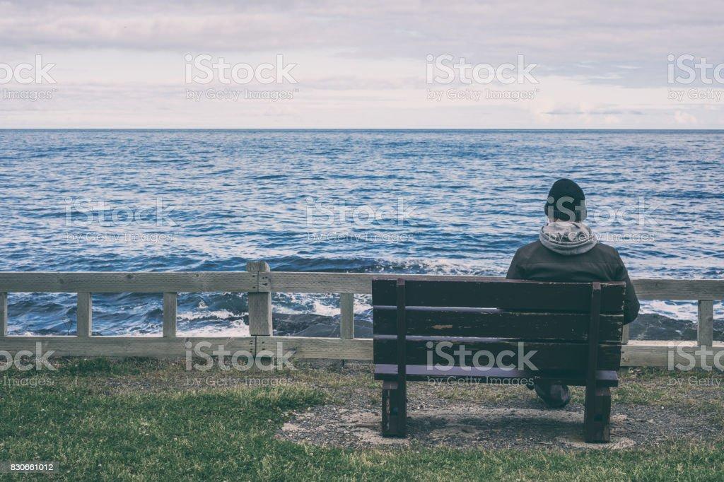 Homem sentado no banco com vista para o mar - foto de acervo