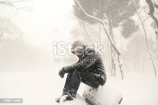 Pensive man sitting on bench snowy day