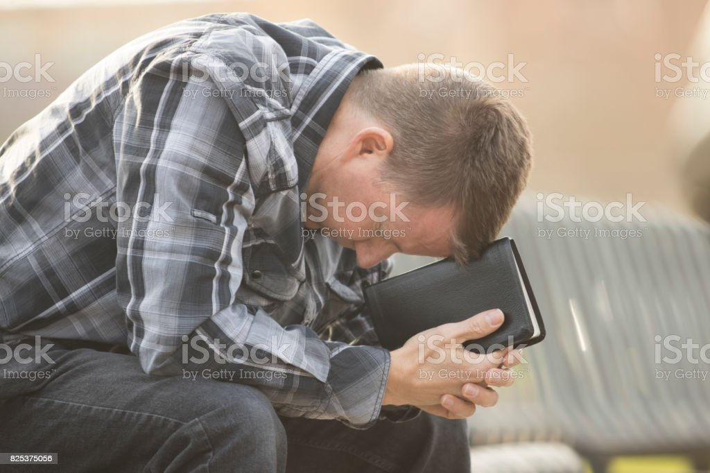 Man sitting on bench with Bible stock photo