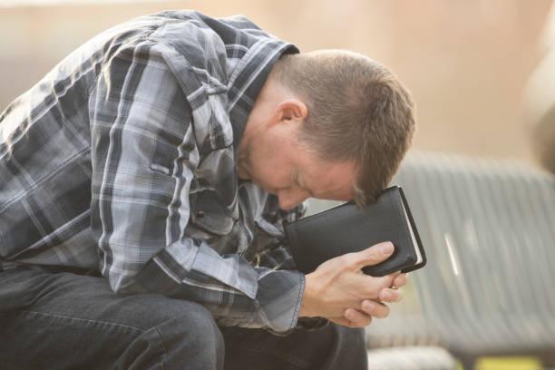 男人坐在長椅上與聖經 》 - prayer 個照片及圖片檔