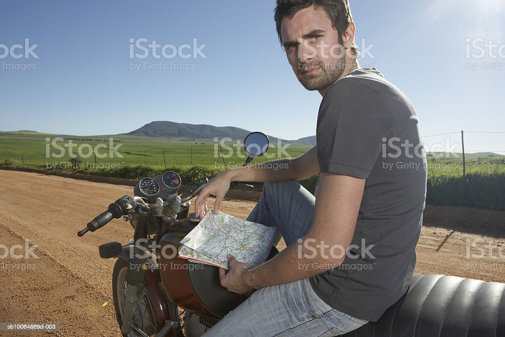 Man sitting on bike, holding map, portrait foto royalty-free