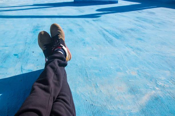 mann sitzt auf blauem boden sicht - sweatpants stock-fotos und bilder