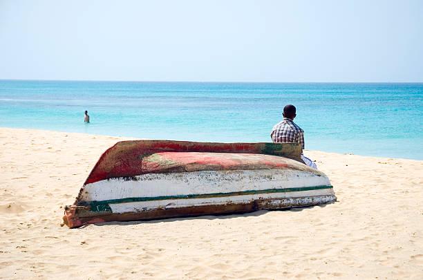 mann sitzt auf einem boot am herrlichen strand. - kapverdische inseln stock-fotos und bilder
