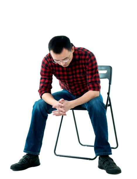 mann auf stuhl sitzend und denken - rot bekümmerte möbel stock-fotos und bilder