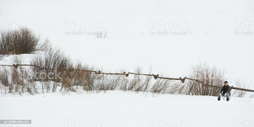 Man sitting on chair in snow royalty-free stock photo