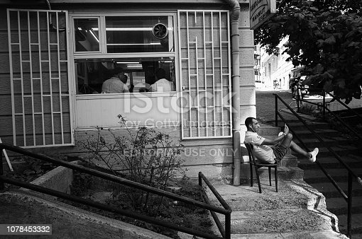 Istanbul, Turkey - September, 2018: Man sitting on chair outside on the street with smartphone and talking via video call in headphones. Two men inside the building