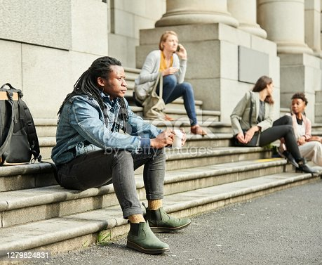 Shot of man sitting on a stairs in the city with females in background