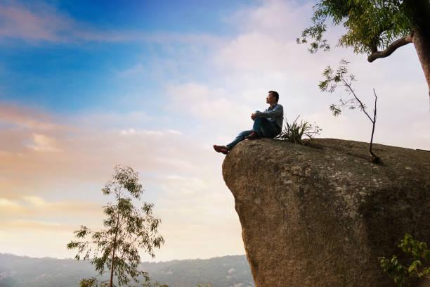 a man sitting on cliff enjoy the view - klif zdjęcia i obrazy z banku zdjęć