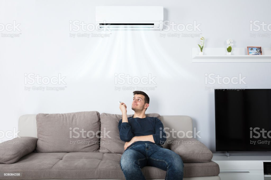 Man Sitting On Couch Operating Air Conditioner stock photo