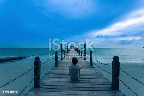 Man sitting alone in front of the ocean