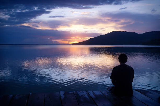 Man sitting on dock with orange sunset on purple blue sky along lake Itza, El Remate, Peten, Guatemala stock photo