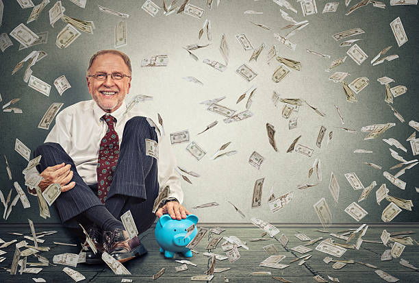 Man sitting on floor with piggy bank under money rain Excited happy senior man sitting on a floor with piggy bank under a money rain isolated on gray wall background. Positive emotions financial success luck good economy concept millionnaire stock pictures, royalty-free photos & images