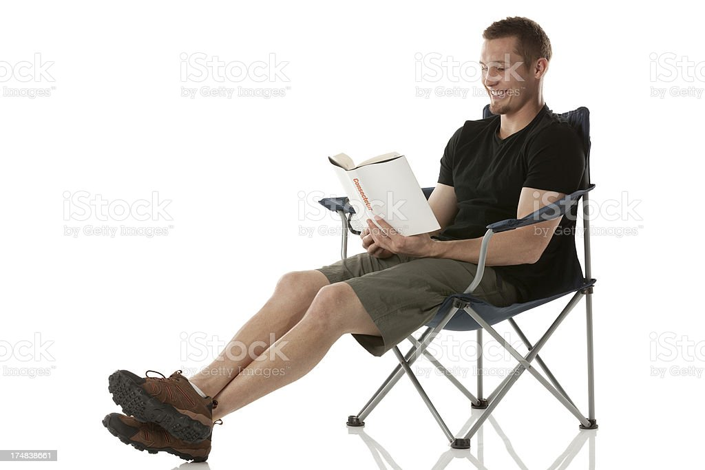 Man sitting on folding chair and reading a book royalty-free stock photo