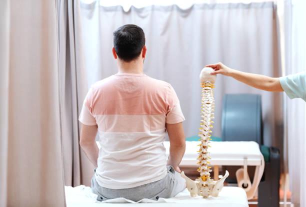 mann sitzt am krankenhausbett mit rücken gedreht. neben ihm doktor holding-modell der wirbelsäule. - rückenschmerzen beim sitzen stock-fotos und bilder