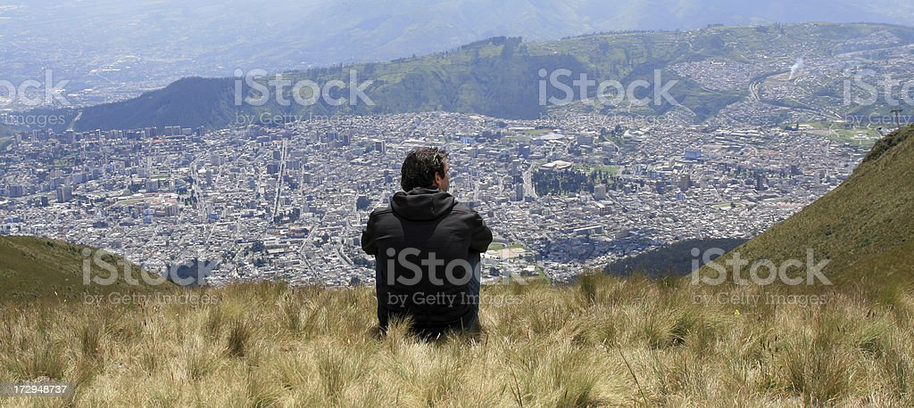 Man Sitting on Mountain Summit Looking City of Quito, Ecuador royalty-free stock photo