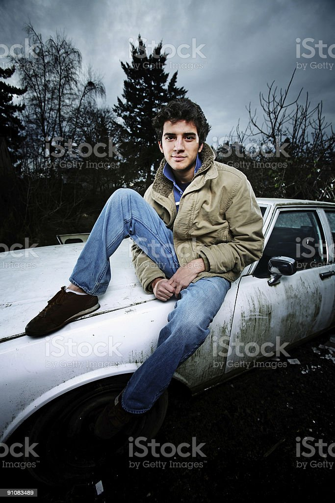 Man Sitting on Old Car Under Dark Sky royalty-free stock photo