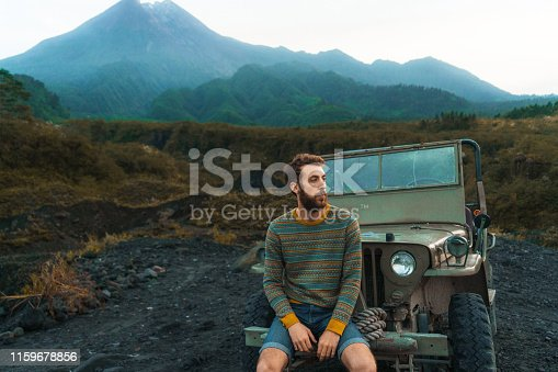 Scenic view of young Caucasian man sitting on old fashioned SUV on the background of Merapi volcano